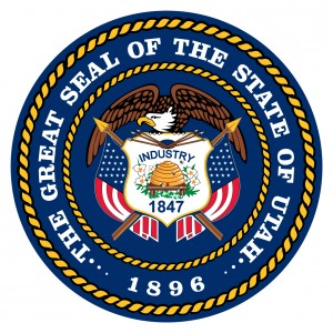 "State seal of Utah featuring a beehive at center on a white shield, flanked by American flags and topped by an eagle with outspread wings. Immediately above the beehive is the word ""Industry."" Immediately below it is the year 1847, the date when the Mormons first settled in the territory."